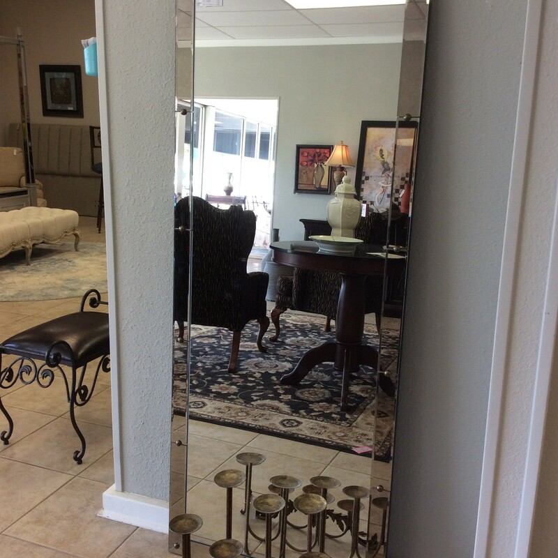 A very tall Uttermost mirror that measures 30x76. This mirror has smoked cut mirror on the sides and has nail heads on each seam. It is very pretty and a very heavy sturdy mirror!