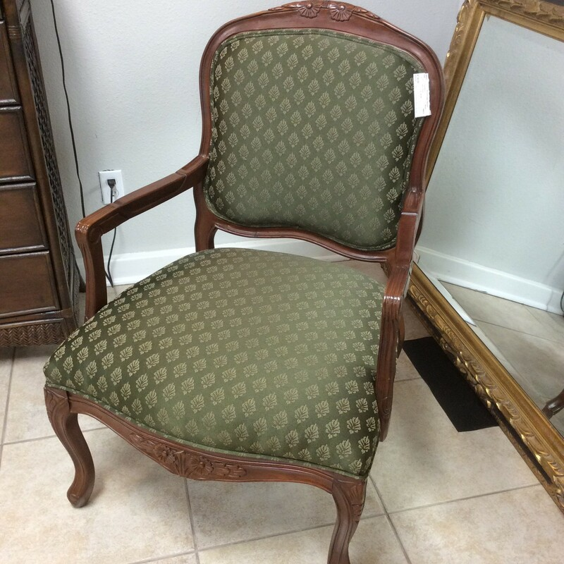 This arm chair features a dark wood finish with lovely carved details and has been upholstered in a deep green with a delicate floral pattern.
