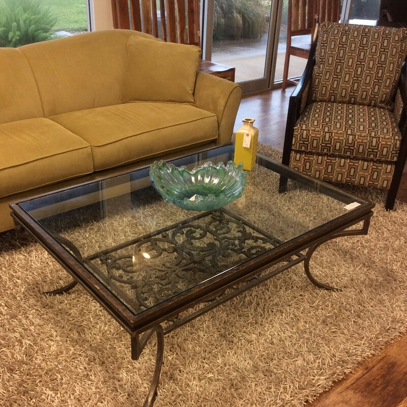 Rectangular glass top coffee table with an iron base and trim. The scrolled base shows through the glass and it has curved iron legs. Black with a slightly gold touch. Measures 48x35x18