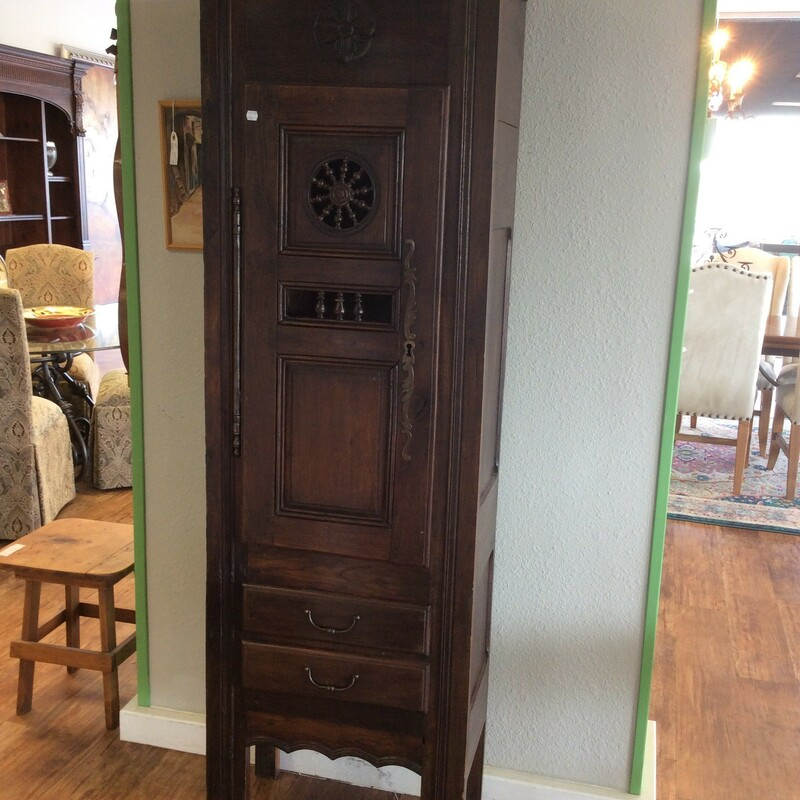 Tall dark wood cabinet with a captains wheel carved on the door. Two drawers on the bottom and two shelves inside of door. The oil rubbed bronze hardware looks to be original to the piece. It also has a unique hinge. Measures 28x13x72