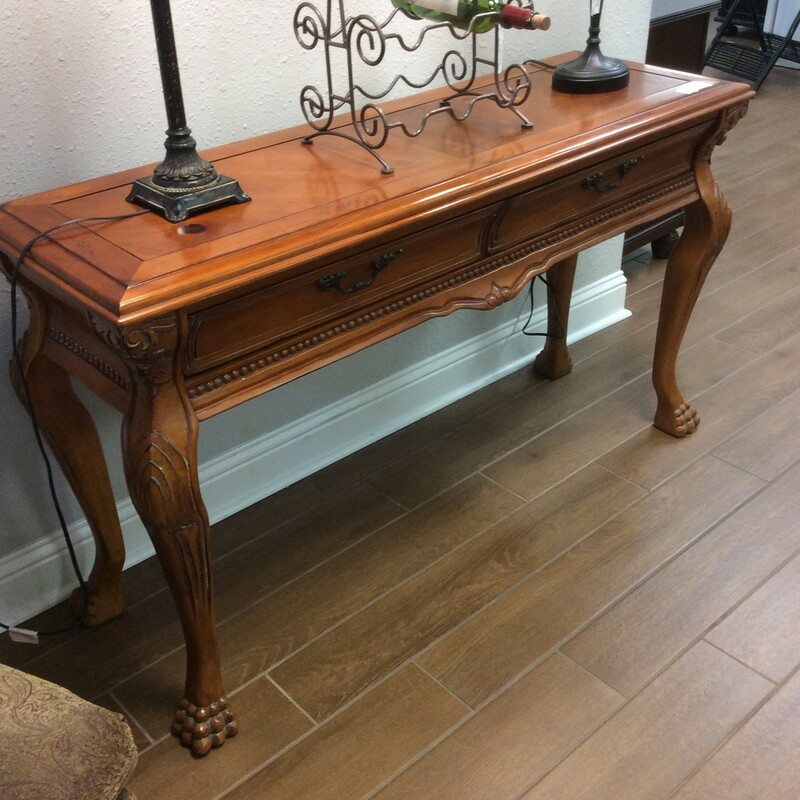 This is a very pretty light oak sofa table with mixed woods. It is carved with beading along the edge and it has slightly curved legs. This table also has two drawers. Measures 54x18x31