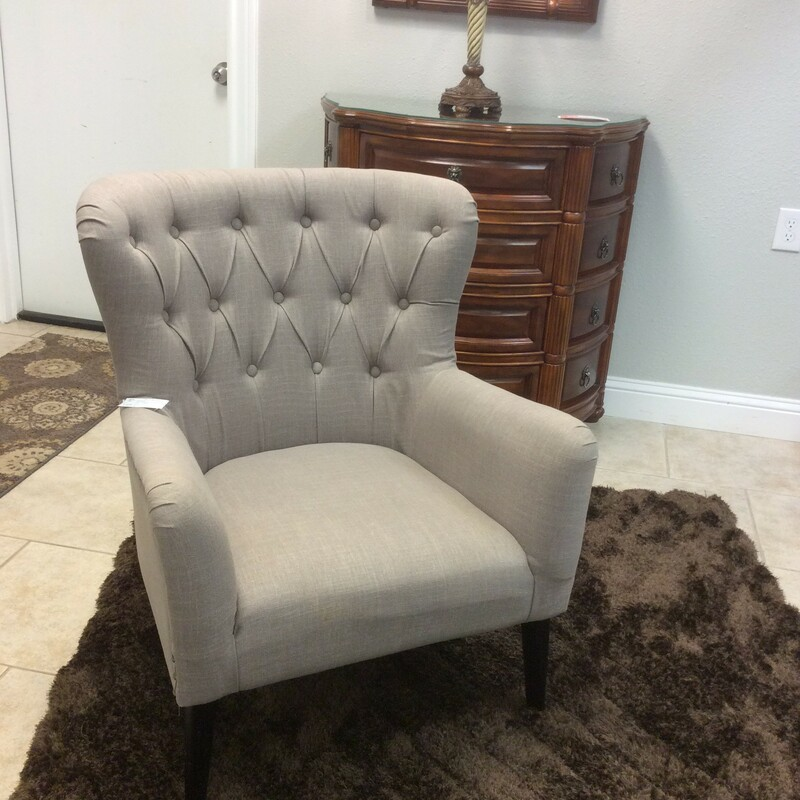 This chair has been upholstered in a soft taupe and has a button-tufting on the seatback.