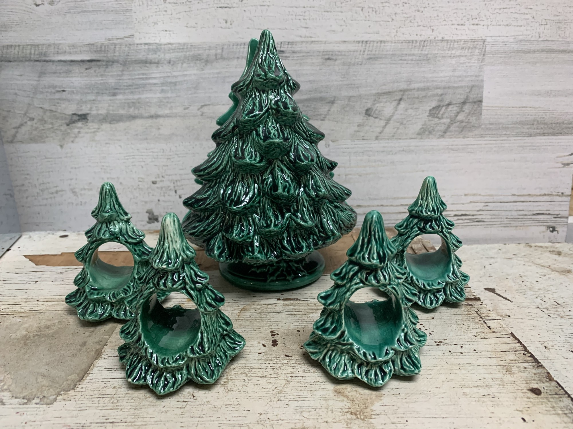 Beautiful vintage ceramic Christmas tree napkin holder, may be used as a card holder, and a set of four (4) napkin rings.<br /> In a good vintage condition, there is a small almost unnoticeable chips on two of the napkin rings. Please make sure to look at all the pictures for a closer visual.<br /> Measures approx. napkin/card holder 7 1/2'' tall, 5 1/4'' wide, 3 1/2 base diameter. Napkin rings 3 1/2'' tall, 2 3/4'' wide, 2 1/2'' base diameter.<br /> Thank you.