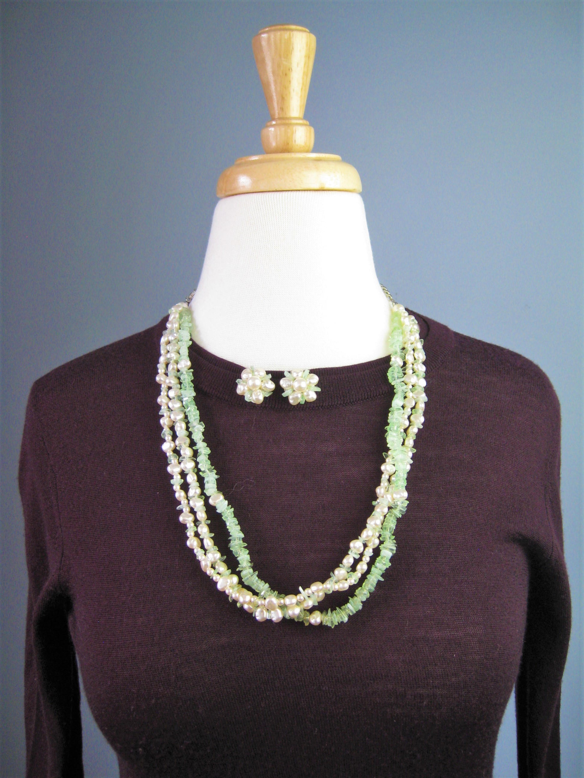 In the old days, ladies always matched their outfits carefully including their jewelry<br /> This set was not necessarily purchased together but look perfect together<br /> Multistrand necklace w green & white stone chips & matching clip earrings w faux pearls & green bits<br /> The necklace can be twisted and worn as a torsade choker. It has an extender section on the chain so you can play with the length.<br /> As shown, the necklace is 26in long.<br /> The earrings are 3/4in across.<br /> <br /> Thanks for looking!