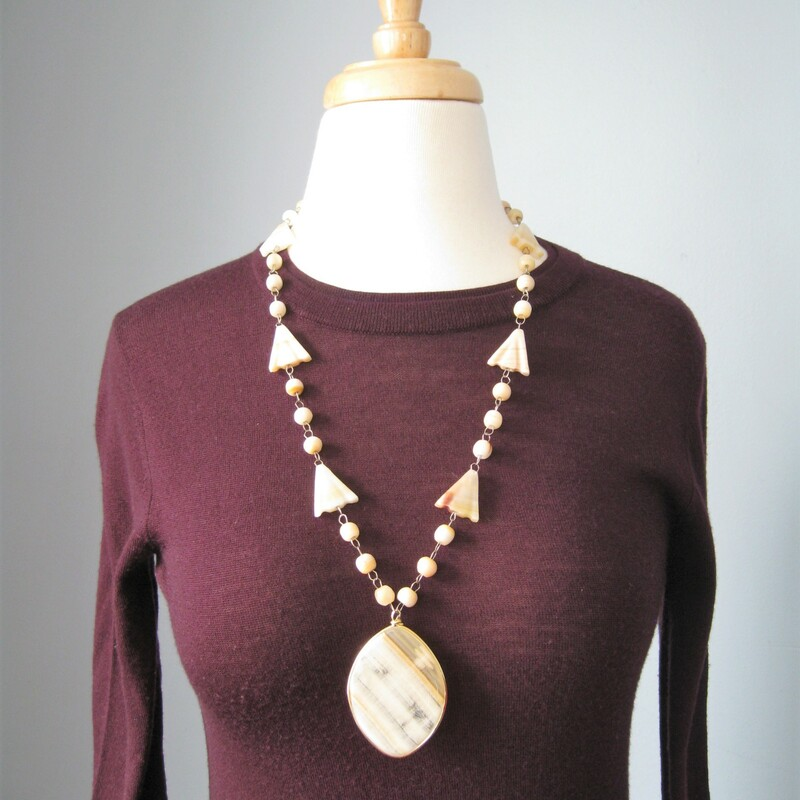 Pendant necklace made of pale ivory round and arrow shaped stone beads on a thin metal wire. Large teardrop pendant of carved stone. The carving is a Sun God or sunburst design   simple hook clasp.  Necklace: 27in long Pendant: 2. 1/2in x 1 3/4in  Thanks for looking!