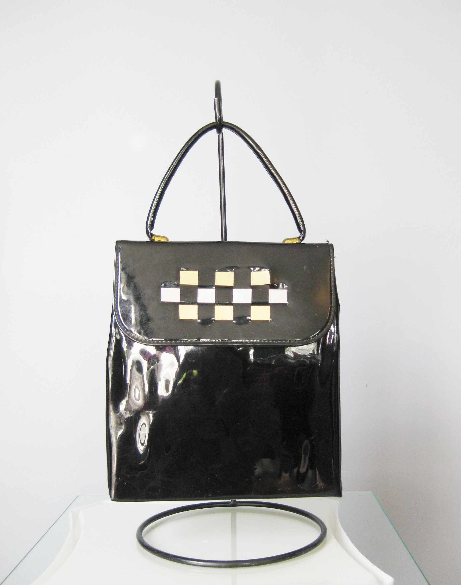 super cute vintage bag in black patent leather<br /> Top Handle, slim style<br /> Three metal foil strips are woven into the flap for decoration.  Two 'gold' ones and a 'silver' one in the middle<br /> No tags<br /> Faille Lining<br /> Snap closure<br /> <br /> The bag is in great shape with some imperfections on the patent leather. No gashes but some dull areas<br /> <br /> Width: 8.5in<br /> Height: 9 1/2in<br /> Depth: 2;5in<br /> Handle drop: 4in<br /> <br /> Thanks for looking!<br /> #13999