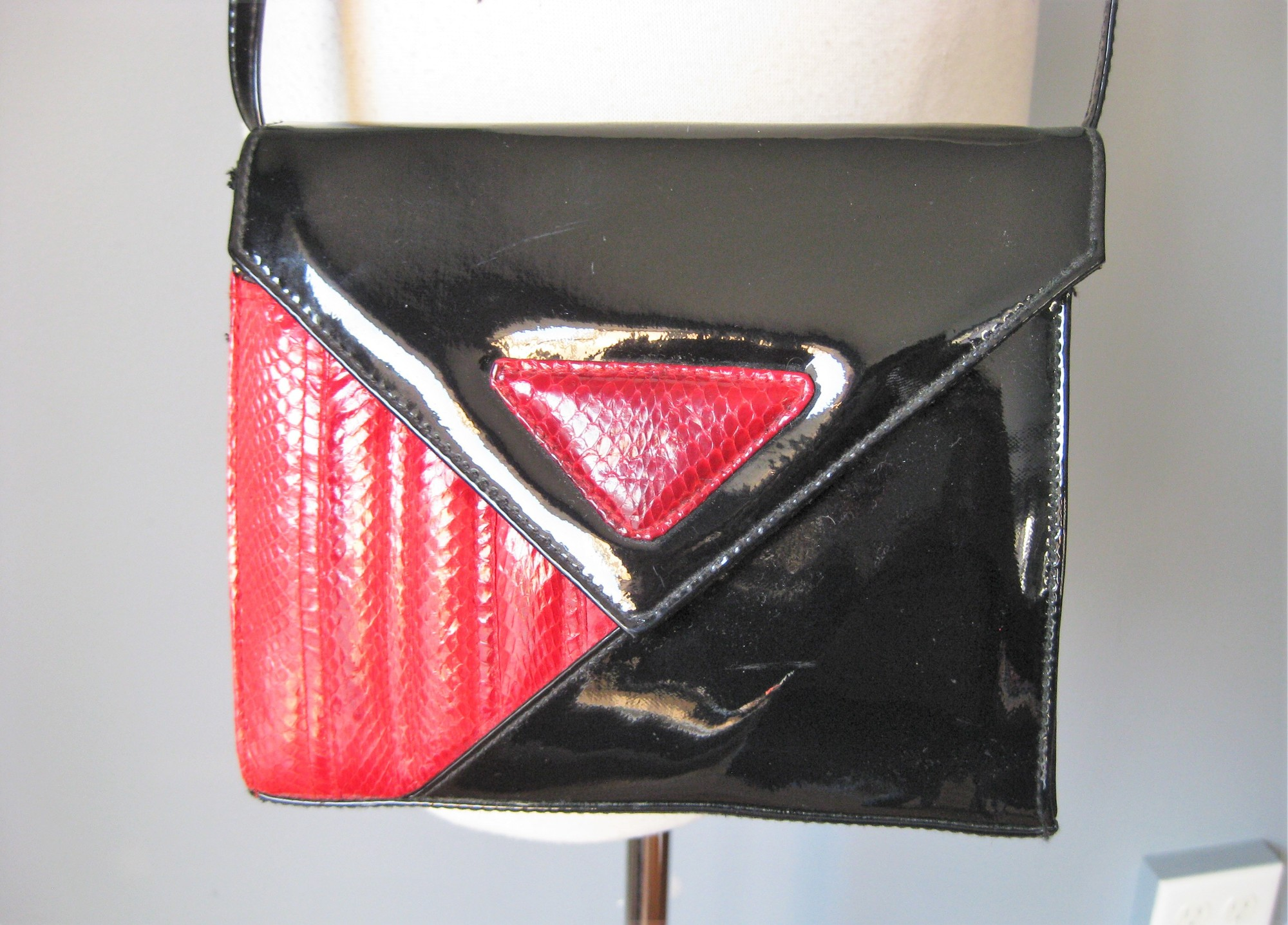 Everything about this purse proclaims its 80s origins<br /> Sharp color combination in red and black<br /> Triangular flap with snap closure<br /> A touch of snakeskin<br /> Long thin patent leather strap.<br /> Handy with one main compartment with a zippered pocket.<br /> Excellent condition, no tags<br /> <br /> 8in x 7in x 3in<br /> Strap drop: 24.5in  (the thin strap can be easily tied anywhere for shorter versions<br /> <br /> Great condition with minor rubs on the patent leather on the bottom of the bag<br /> <br /> thanks for looking!<br /> #14781