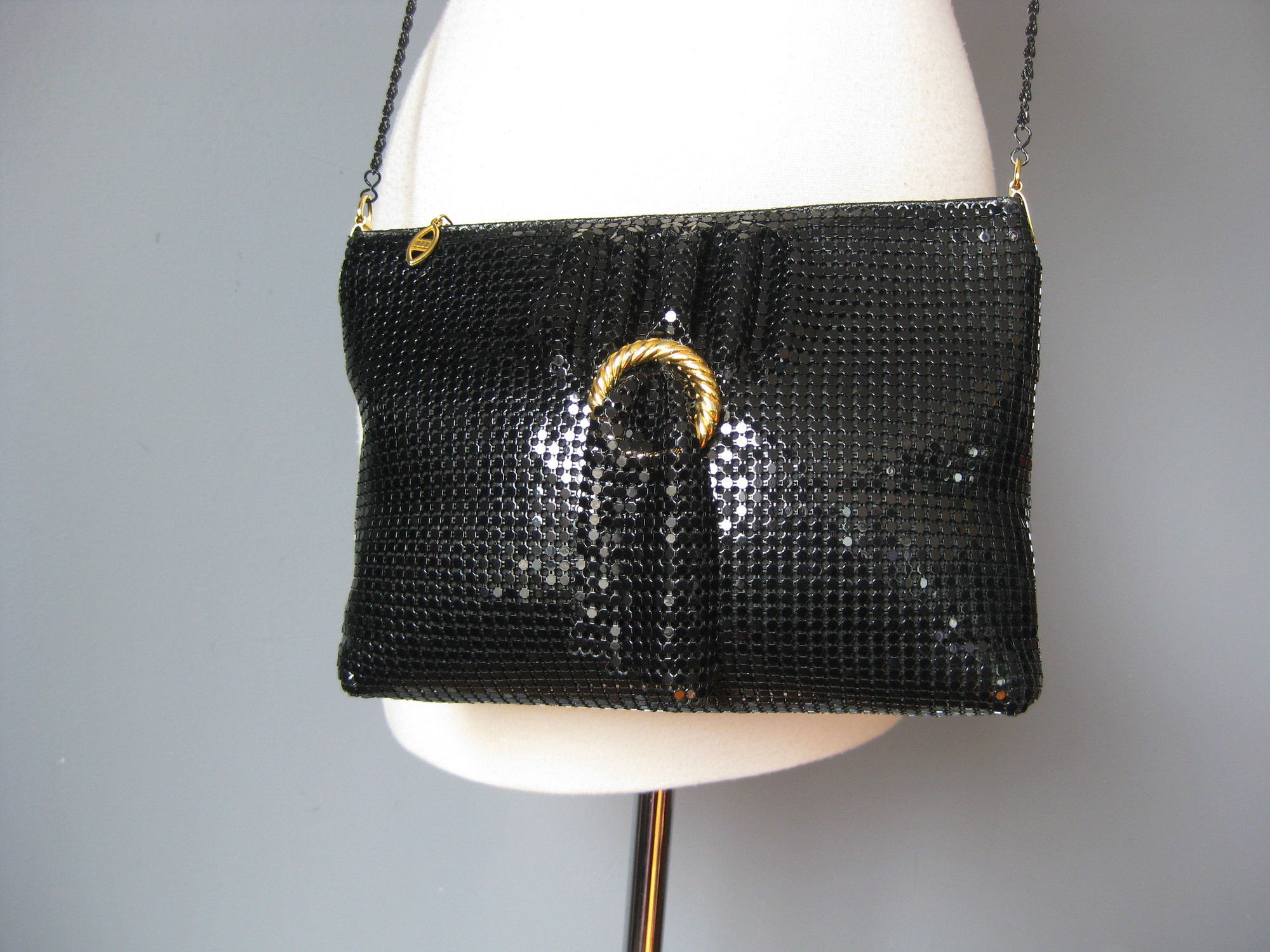 Cool black metal mesh evening bag with a thin black chain strap.<br /> Top Zipper<br /> Just in case the shiny mesh doesn't catch enough light, there is a free swinging swag of mesh at the front poking through a gold ring.<br /> Slim but flexible, will hold everything you need<br /> No tags<br /> I slip pocket inside<br /> Tiny bit of wear on the top edge<br /> 10.5in x 7in x 2in<br /> chain drop: 22in<br /> <br /> Thanks for looking!<br /> #15167