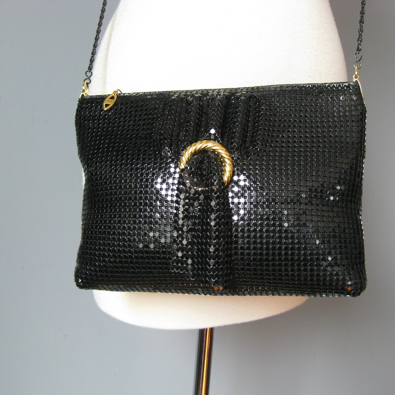 Cool black metal mesh evening bag with a thin black chain strap. Top Zipper Just in case the shiny mesh doesn't catch enough light, there is a free swinging swag of mesh at the front poking through a gold ring. Slim but flexible, will hold everything you need No tags I slip pocket inside Tiny bit of wear on the top edge 10.5in x 7in x 2in chain drop: 22in  Thanks for looking! #15167