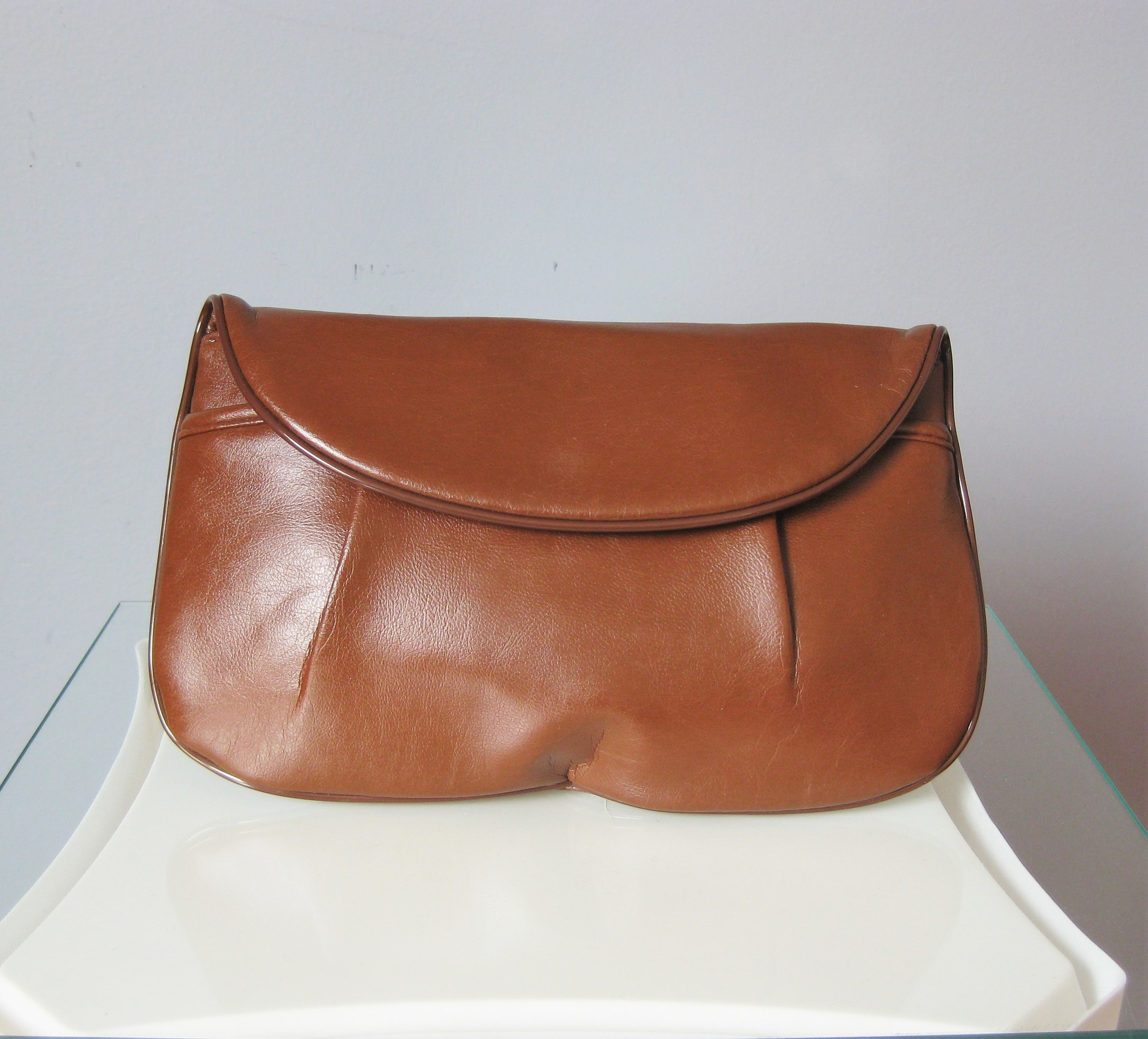 Super simple faux leather clutch in the warmest brown tone ever.<br /> Rounded shape with two compartments and a flap with snap closure<br /> Brand tag missing<br /> Excellent.  There is a mark on the inside of the flap as shown.<br /> <br /> The bag measures 10 1/2in by 6 5/8in<br /> <br /> Thanks for looking!<br /> #15209