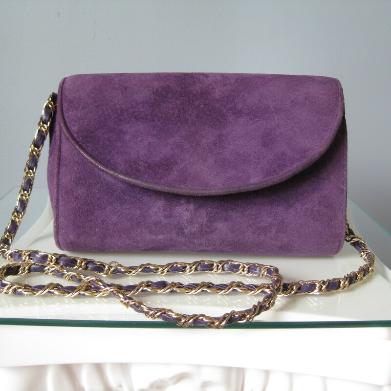 Perfect little bag for evening in a great color. made of genuine purple suede with a long gold chain strap woven with purple leather the flap has a snap closure  good size, I can easily fit my phone in its wallet style case in there with room to spare for other essentials.  Excellent condition! The only wear is along the edge of the flap as shown in one of my photos.  width: 8 1/4in height: 5 1/2in depth: 1 5/8in chain drop: 19in  thanks for looking!