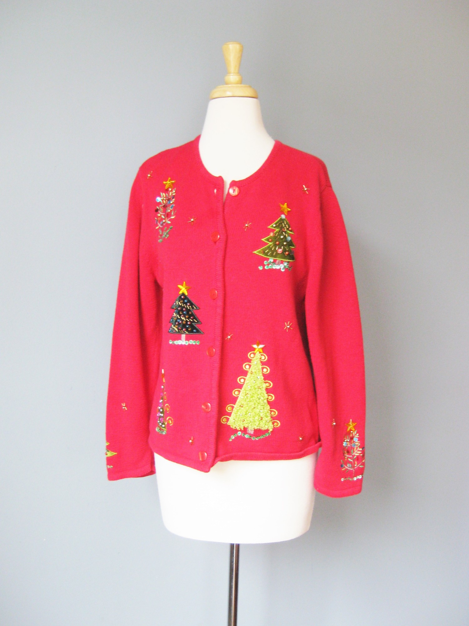 very pretty red cardigan with a Cheery Christmas Theme.<br /> Really nicely worked Tree appliques, and beading, even on the sleeves<br /> by<br /> Krystal Kobe<br /> Size M<br /> 55% ramie<br /> 45% cotton<br /> red plastic buttons<br /> Flat measurements:<br /> armpit to armpit: 19.5in<br /> width at hem: 20.25in<br /> underarm sleeve seam length: 16in<br /> length: 22.25in<br /> <br /> perfect condition<br /> Thanks for looking1<br /> #15943