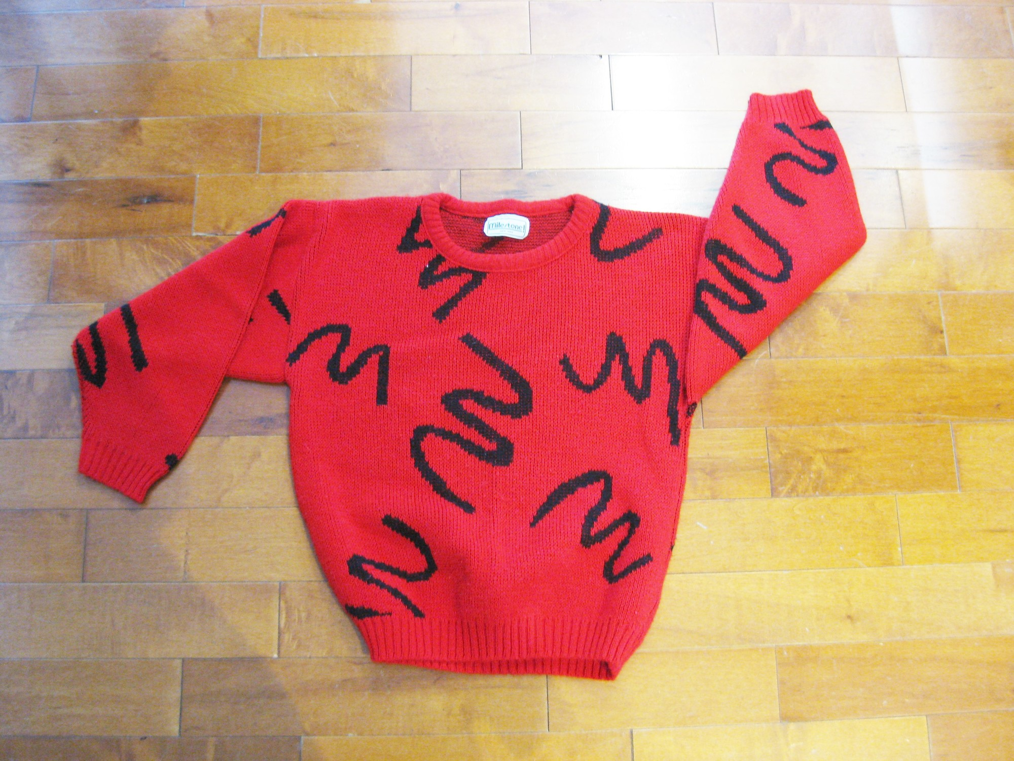 This red and black graphic sweater is so fun.<br /> Abstract black squiggles on a red background<br /> It's made of acrylic and machine washable.<br /> It's rather lightweight<br /> Pulls over the head<br /> <br /> Here are the flat measurements, please double where appropriate:<br /> Shoulder to shoulder: 19.5in<br /> Armpit to armpit: 19in<br /> Width at hem: 15 1/2in<br /> Underarm sleeve seam length: 17in<br /> Overall length: 21.5in<br /> <br /> Thanks for looking.<br /> #18038
