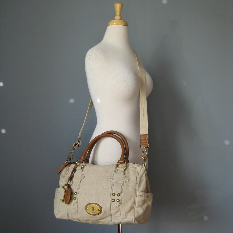 fabulous Fossil satchel in beige canvas with brown leather trim. Double leather handles and a detachable adjustible web shoulder strap Antique brass hardware Key bag charm and leather luggage tag two exterior slip pockets on the sides Chevron striped fabric lining  Super clean inside and out tiny bit of use on the brass hardware medallion  13in x 9in x 5in Handle drop: 6.25in Strap drop at max: 24.5in  Thanks for looking! #18049  Please see my eBay store for other terrific Fossil and other bags