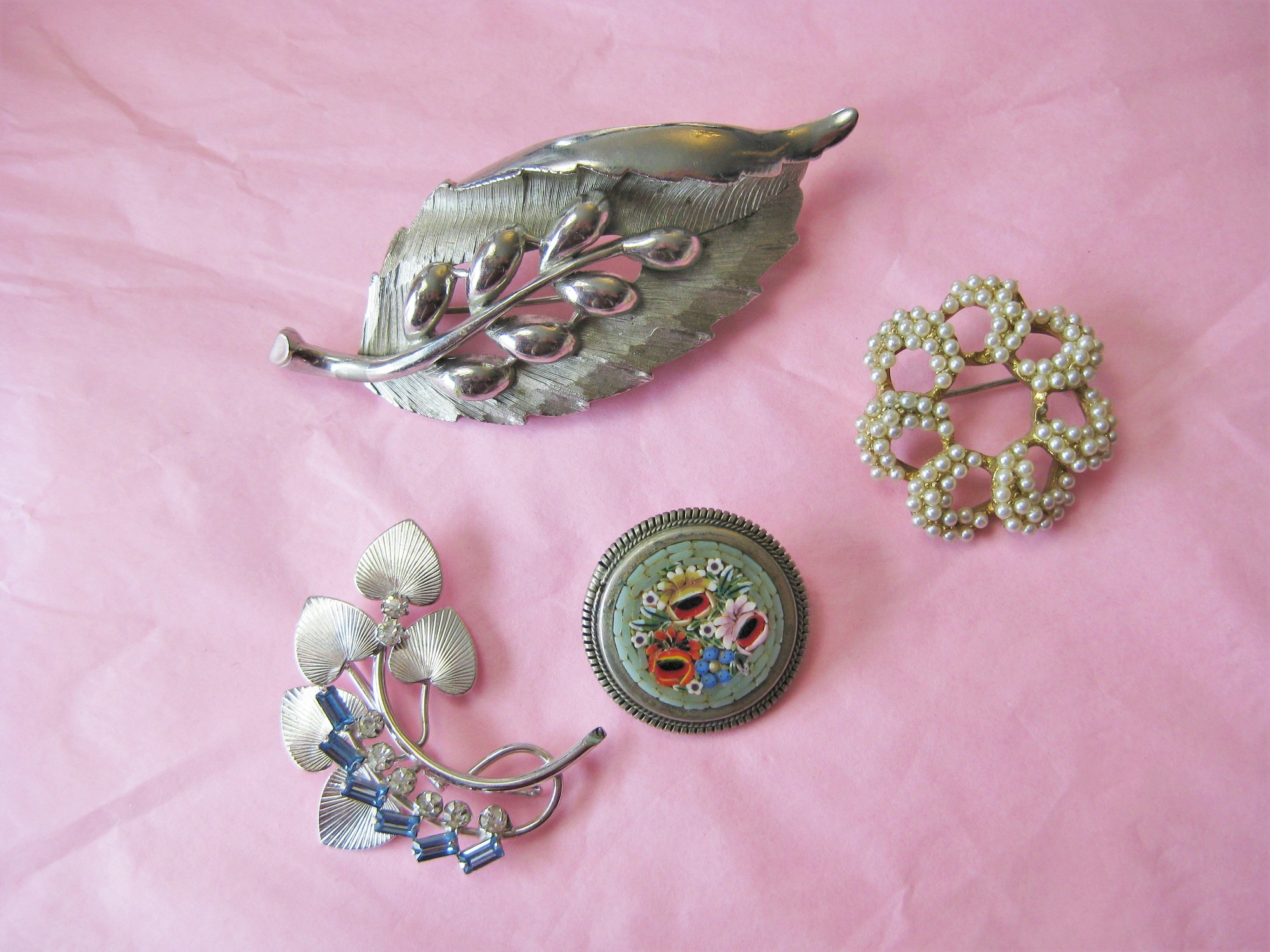 This is a pretty collection of vintage costume brooches.<br /> <br /> The collection consists of:<br /> a. Round gold tone pin with tiny seed pearls, probably faux 1.25in<br /> b. Round micromosaic floral on silver, probably sterlign 1in<br /> c. Modernist silver leaf brooch with gorgous square cut blue rhinestones and round clear ones 1 1/2in<br /> d. Large statement silver tone leaf 4.25in<br /> <br /> Thanks for looking!<br /> #18056