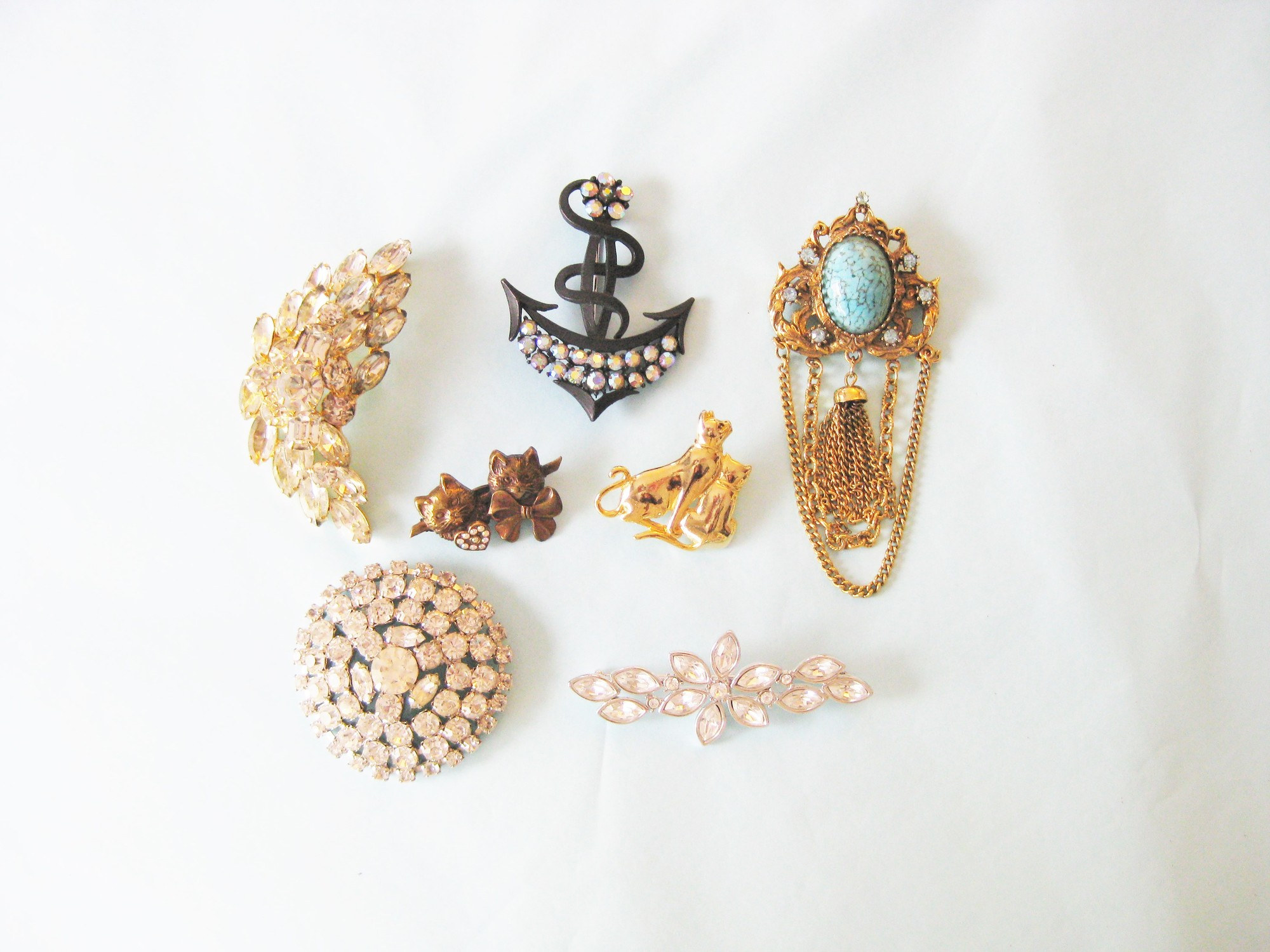 This is a pretty collection of vintage costume 1960s statement brooches<br /> <br /> The collection consists of:<br /> a. Round Rhinestone Coat Pin 2.5in diameter, the pin is bent but works fine, it might have been made this way to accomodate the thickness of a coat?<br /> b. Signed Monet straight floral pin with large rhinestones<br /> c. Faux turquoise with blue rhinestones and dangling chains<br /> d. Crescent leaf pin in rhinstones set in gold<br /> e. Black metal Anchor with irridescent rhinestones<br /> f. Antiqued coppery gold tone pin, two sweet cats with a little circle of tiny rhinestones<br /> g. Gold cat pin, a mother and her kitten.<br /> <br /> All in great shape, I have photos of the back of each pin, lmk if you'd like to see any of them.<br /> <br /> Thanks for looking!<br /> #36068