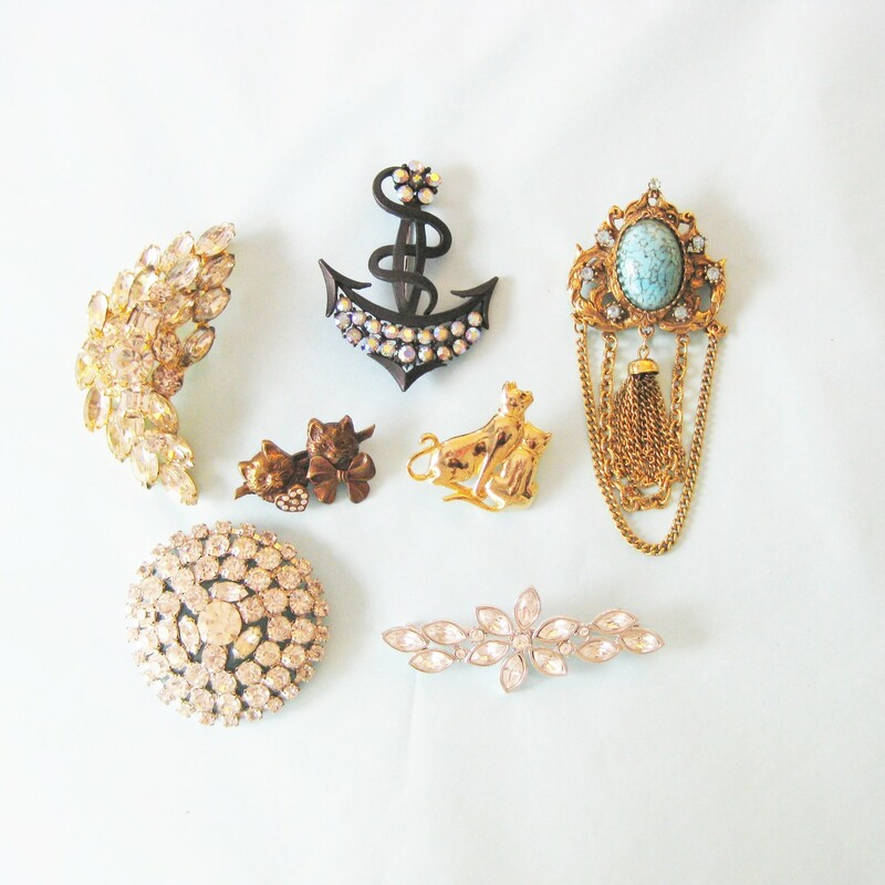 This is a pretty collection of vintage costume 1960s statement brooches  The collection consists of: a. Round Rhinestone Coat Pin 2.5in diameter, the pin is bent but works fine, it might have been made this way to accomodate the thickness of a coat? b. Signed Monet straight floral pin with large rhinestones c. Faux turquoise with blue rhinestones and dangling chains d. Crescent leaf pin in rhinstones set in gold e. Black metal Anchor with irridescent rhinestones f. Antiqued coppery gold tone pin, two sweet cats with a little circle of tiny rhinestones g. Gold cat pin, a mother and her kitten.  All in great shape, I have photos of the back of each pin, lmk if you'd like to see any of them.  Thanks for looking! #36068