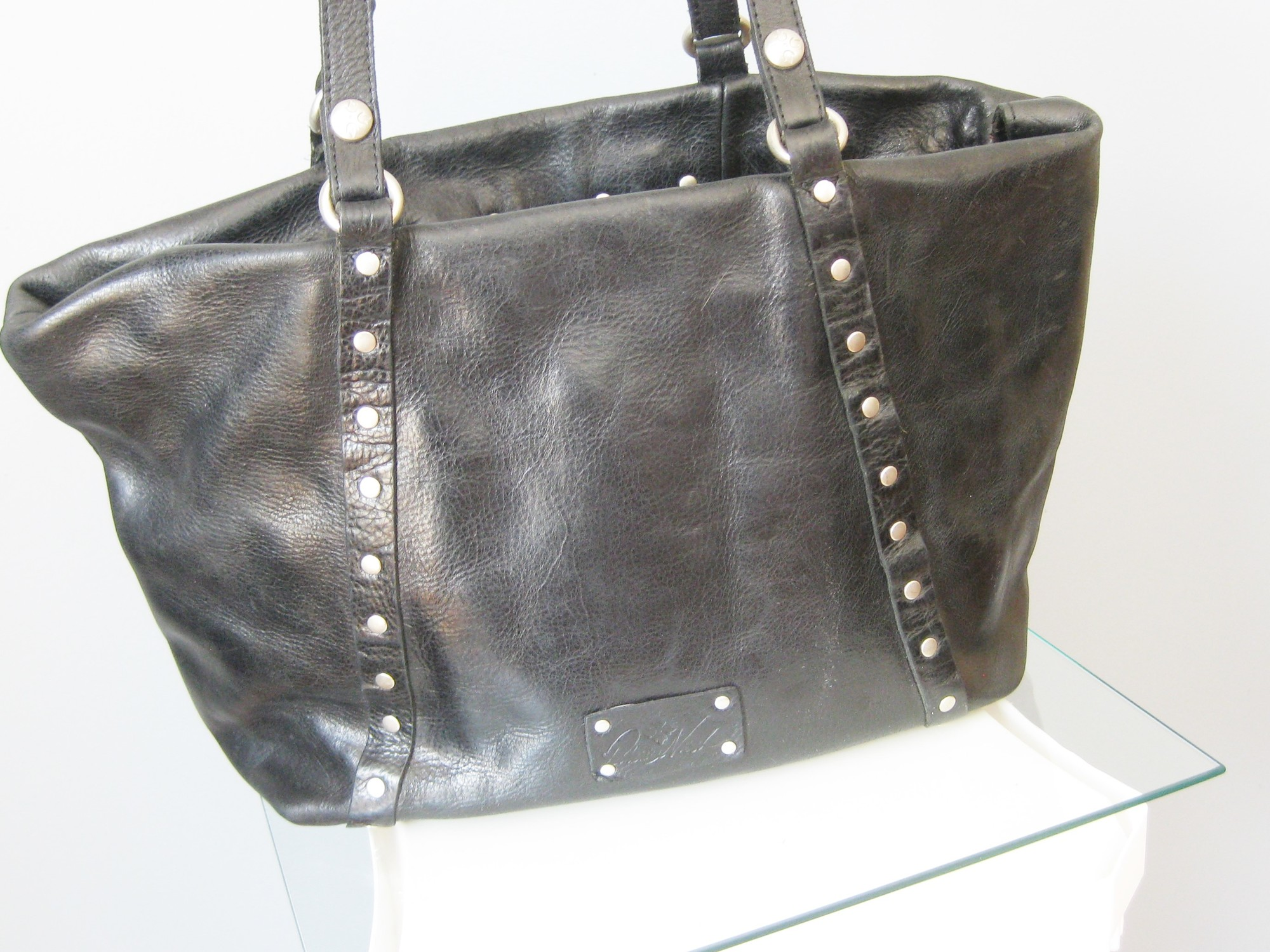 Awesome leather tote by<br /> Patricia Nash<br /> Silvi Model<br /> This work horse bag is made of tough black leather and has silver tone rivets attaching the double straps.<br /> Bag and deep this bag will hold it all nicely.<br /> It has a metal plate/turn lock closure and unfortunately one of the turn lock parts is missing. Please see the photos.<br /> You may carry this bag with the top edge folded down , leaving it unlocked and so this might work for you.<br /> You can still secure the top nicely with the one turnlock that is still present<br /> otherwise super condition, clean inside and out.<br /> <br /> 13.5in x 10in x 7in at the bottom<br /> <br /> thanks for looking!<br /> #38096