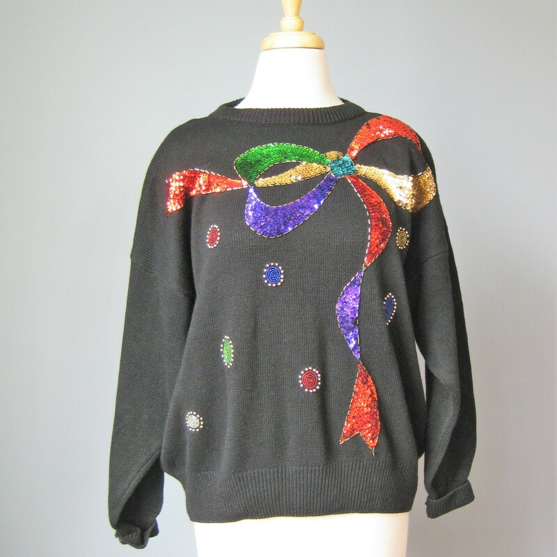 Bonnie Evans Bow Sequin, Black, Size: XL Gorgeous vintage sweater decorated with a giant sequined bow at the shoulders with long ribbons trailing down the front. It's made of a cotton ramie blend and it's by Bonnie Evans Crew neck, dropped shoulder  Marked size 18, but seems a bit smaller than that Flat Measurements: Armpit to Armpit: 26in Underarm sleeve seam length: 18in Width at bottom : 19in Length: 24in Excellent condition  Thank you for looking #40205