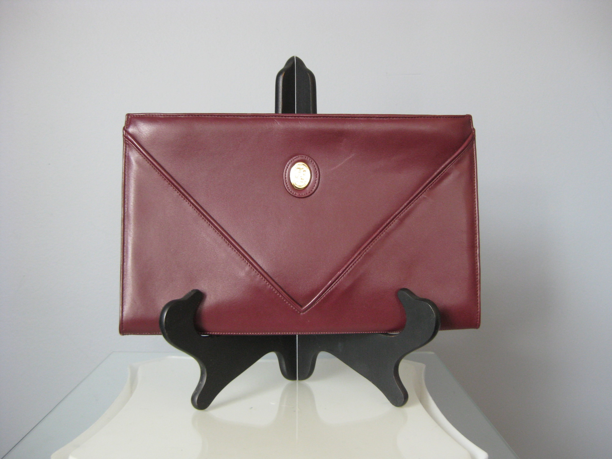 This is an understated but rich looking slim clutch made of fine burgundy leather by FS Originals   It has two compartments and opens at the top with a zipper.   Inside it has one zippered pocket.<br /> Made in Korea<br /> Excellent condition<br /> <br /> I love the large scale of this clutch.  Makes a statement and is actually roomy enough to be practical for a day look.<br /> <br /> The bag measures 11.75in by 7.25in and is about 1in deep without anything in it.<br /> Thank you for looking.<br /> <br /> #40965