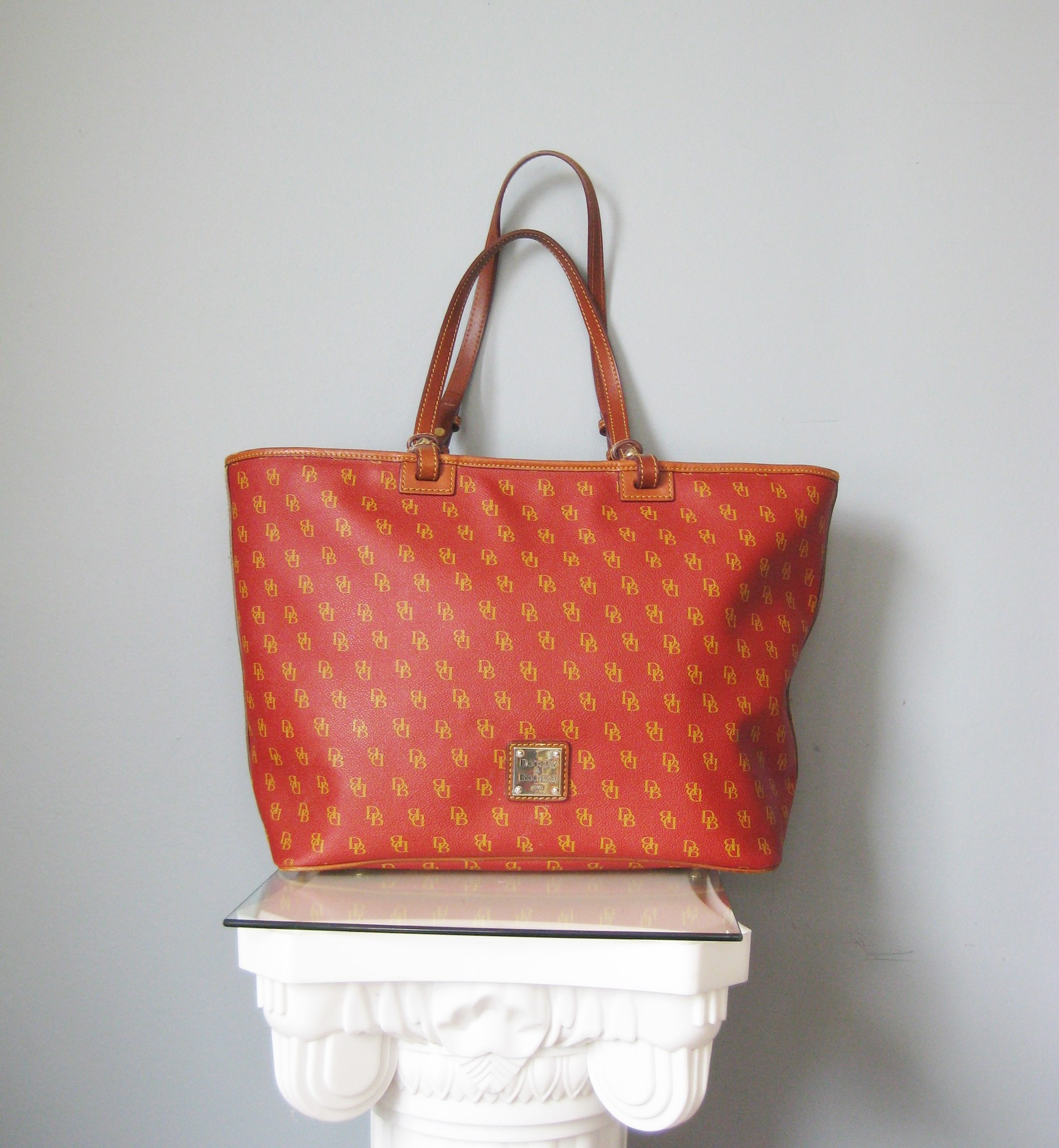 Dooney & Bourke Satchel, Red, Size: None<br /> Gorgeous Dooney & Bourke carryall tote in a deep orange red, so perfect for summer and fall.<br /> Classic and chic shape and super roomy.<br /> The body is coated logo printed leather the trim is brown leather<br /> Double handles<br /> Key clip inside<br /> Interior zippered pockets and slip pockets, one with a snap<br /> <br /> PERFECT condition outside<br /> fair amount of marks on the bottom of the lining inside.<br /> <br /> 18in x 11in x 7in<br /> Handle drop: 12in<br /> <br /> thanks for looking!<br /> #41138
