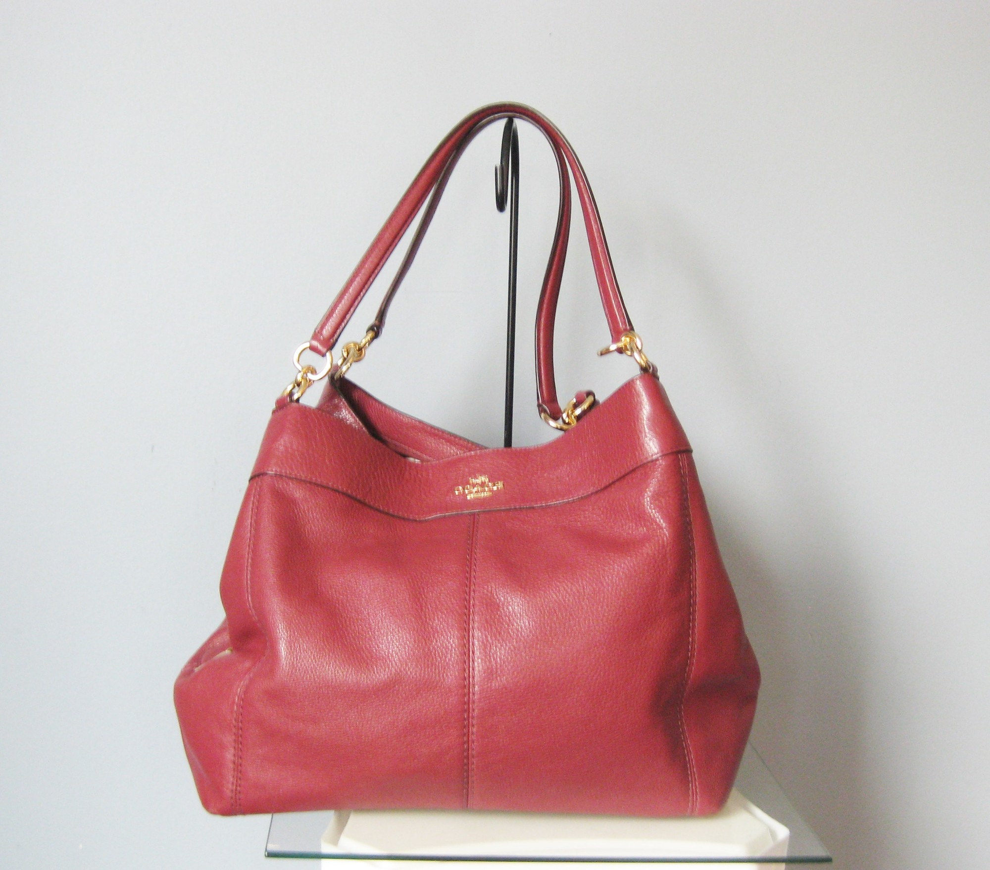 Coach Leather 23511, Burgundy, Size: None<br /> Gorgeous dark red leather Madison Phoebe bag from Coach.<br /> Three main compartments, the outside two snap together at the top and the middle one has a zipper.<br /> Nice and secure for travelingt<br /> also roomy!<br /> 16in x 12in x 6in<br /> handle drop : 9in<br /> Two slip pockets and one zippered pocket inside<br /> <br /> immacualte inside and out.<br /> <br /> Thanks for looking!<br /> #41444
