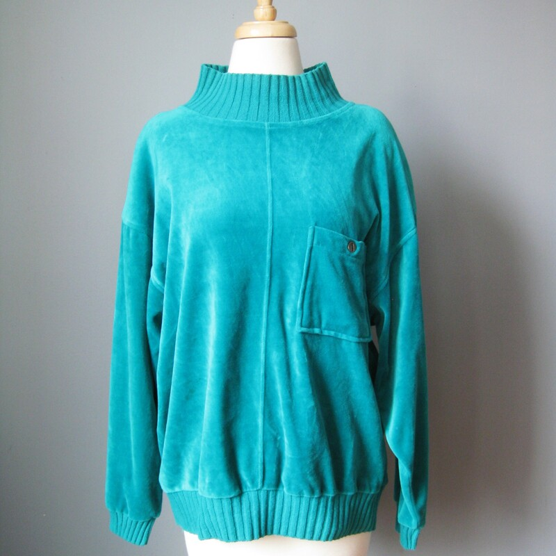 Cozy vintage velour sweatshirt style top from Pacer made in the 1980s Teal leaning toward turquoise Funnel neck Chest pocket Long sleeves Shoulder pads made in Korea  size medium flat measurements: armpit to armpit: 23 1/2in length: 23in 78% cotton 22% poly  excellent condition! Thanks for looking!