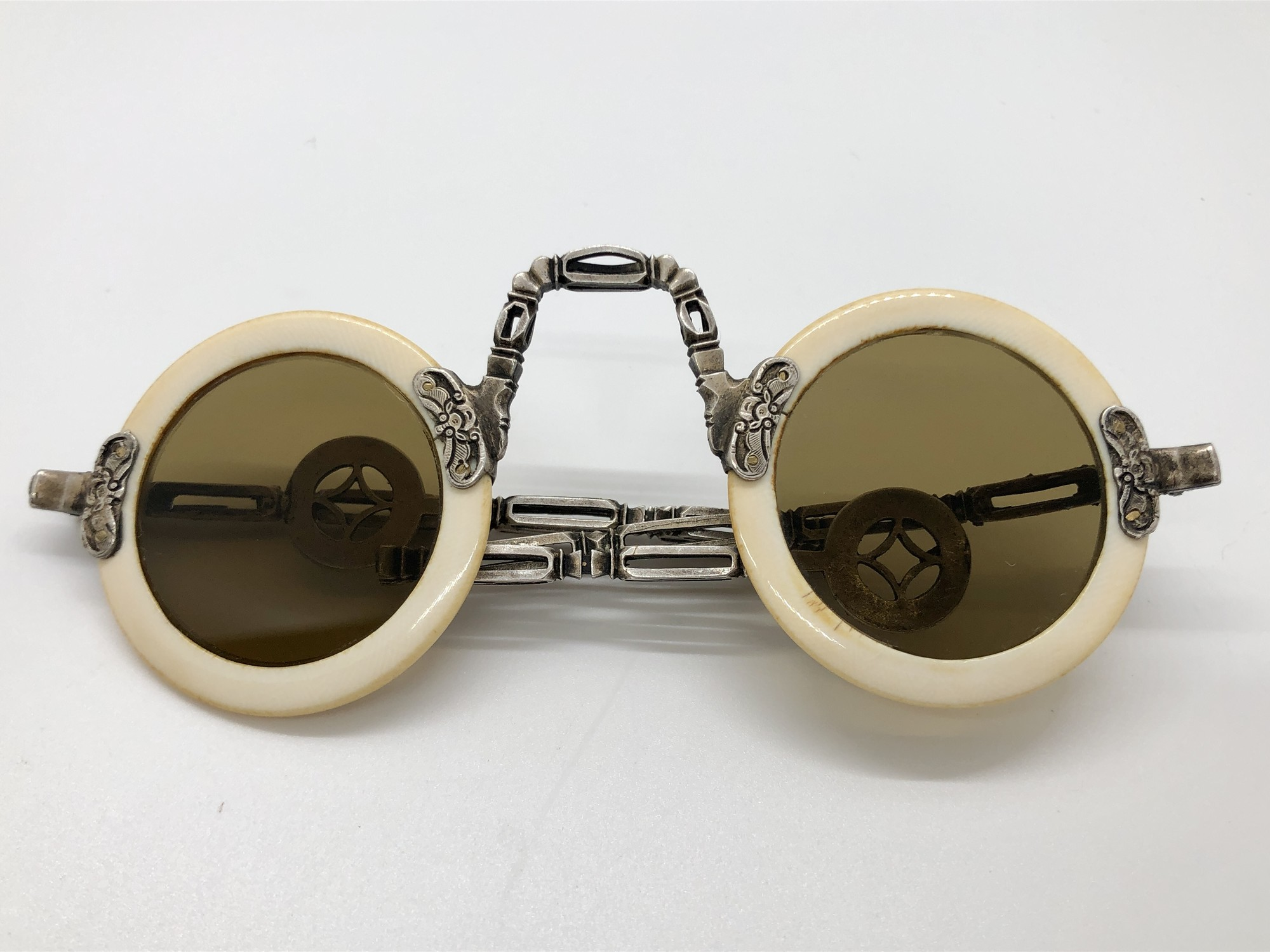 Qing Dynasty Chinese Round Sunglasses. Rims made of  bone and lenses are smokey quartz. Beautifully crafted white metal open work, articulating arms and coin shaped ends c.1800s.<br /> Will ship USPO priority mail.