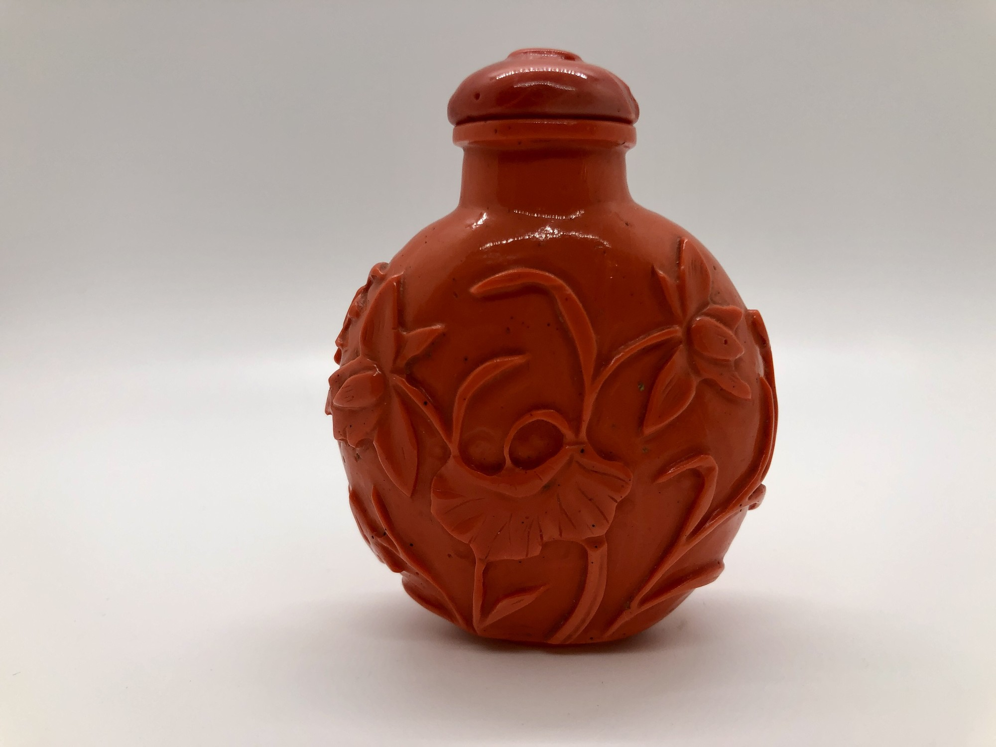 """Wonderful large c. 19th century Chinese Qing Dynasty Peking glass snuff bottle made to imitate coral. Carved with  lotus flowers and leaves. Lid has a small chip.<br /> 3\"""" x 2.25\"""""""